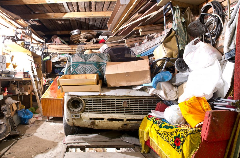 Garage inside. Old broken car, shelves with tools and stacks of things.