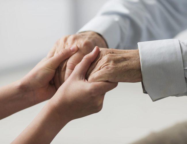 nurse-holding-senior-man-s-hands-for-sympathy