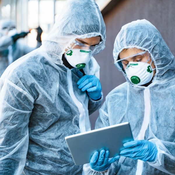 Healthcare,Workers,Wearing,Hazmat,Suits,Working,Together,To,Control,An